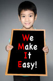 Asian boy  with WE MAKE IT EASY! message on black board Royalty Free Stock Photography