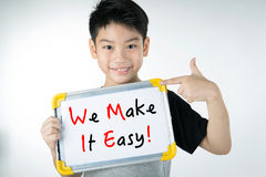 Asian boy  with WE MAKE IT EASY! message on white board Stock Image