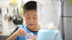 Asian boy making Fresh Fruit Smoothie in kitchen stock video footage