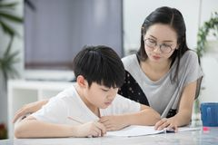 Asian boy with mother teaching and learning your homework at home stock photo