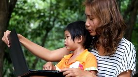An asian boy and mother are using notebook computer at the park. An asian boy and mother are using notebook computer stock video