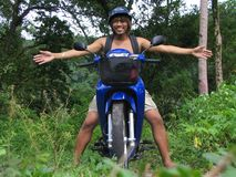 Asian boy on motorcycle in jungle. Asian boy on motorcycle with helmet spreading arms (welcome gesture) in a tropical rain forest or jungle stock images
