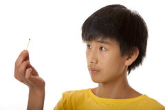 Asian boy observing burned out match Royalty Free Stock Photos