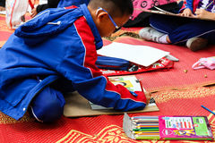 The asian boy is painting crayon color on her drawing for drawi Stock Image