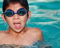Asian  boy peaks  out of the  water. Asian  boy peaks out of the water with his  head while in an outdoor swimming pool Stock Images