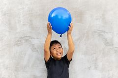 Asian boy play catches balloon on grey background. Asian boy play catches balloon on grey background royalty free stock photography