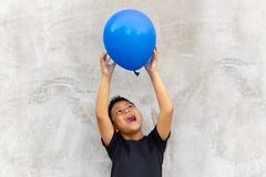 Asian boy play catches balloon on grey background. Asian boy play catches balloon on grey background stock image