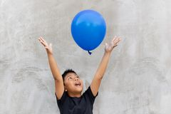 Asian boy play catches balloon on grey background. Asian boy play catches balloon on grey background royalty free stock photo