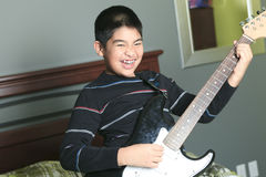 Asian boy play guitar in his bedroom Royalty Free Stock Images