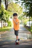 Asian boy play skateboard Stock Photos