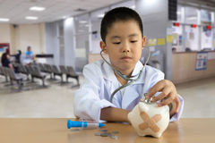 Asian boy playing as a doctor care Piggy Bank. Asian boy playing as a doctor care Piggy Bank Royalty Free Stock Images