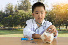 Asian boy playing as a doctor care Piggy Bank.  Royalty Free Stock Photo