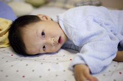 Asian boy playing on the bed with blue pajamas Stock Photography