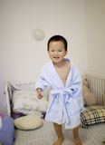 Asian boy playing on the bed with blue pajamas Stock Photo