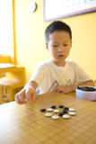 Asian boy playing the game of  I-go Royalty Free Stock Image