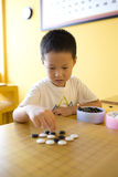 Asian boy playing the game of  I-go Royalty Free Stock Photos