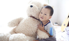 Asian boy playing with his toy bear stock photos