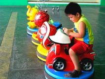 Asian boy playing with kiddie rides. Photo of an asian boy playing with kiddie rides in a grocery store Royalty Free Stock Photography
