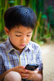 Asian boy playing mobile phone Stock Images