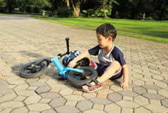 Asian boy playing near his bicycle Stock Images