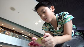 Asian boy playing phone in mall. stock footage