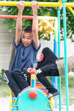The asian boy is playing  a playground  on blurred tree backgroud village of funny Royalty Free Stock Photography
