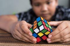 Asian boy playing with rubik`s cube.boy solving puzzle. Brainstorming and brain teaser toy Stock Photos