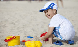 Asian boy playing sand on the beach Royalty Free Stock Photo