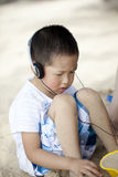 Asian boy playing sand with earphone Royalty Free Stock Images