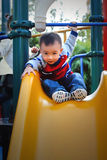 asian boy playing the sliding board Stock Photo