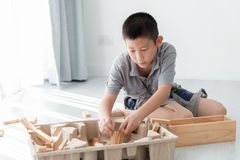 Asian boy playing a Structure from Wooden Blocks Royalty Free Stock Photos