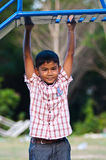 Asian boy playing swing at playground Stock Image