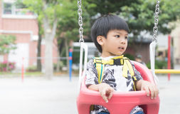 Asian boy playing on the swing Stock Photos