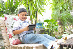 Asian boy playing tablet. At the park Royalty Free Stock Images