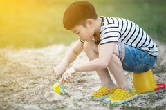 Asian boy playing with toys in garden Royalty Free Stock Images
