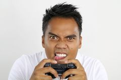 Asian boy playing video games. Young man playing video games with a control pad Royalty Free Stock Image