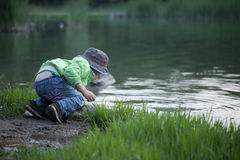 Asian boy playing water. Near a pond Royalty Free Stock Photo