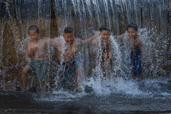 Asian boy playing at waterfall stock photos