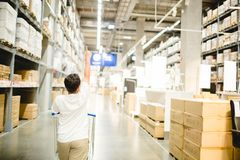 Asian boy is pointing their fingers to choose products and pushing a shopping cart in warehouse for shopping royalty free stock images