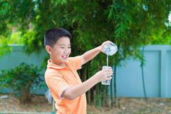 Asian boy pouring water into glass from bottle, Stock Photos