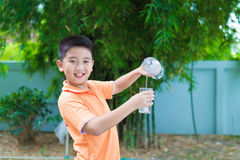 Asian boy pouring water into glass from bottle, Royalty Free Stock Photography