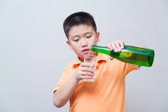 Asian boy pouring water into glass from a green bottle, Royalty Free Stock Photography