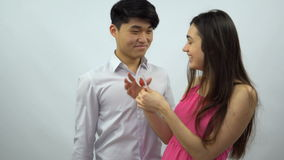 Asian boy presents Valentine card to girl on a white background stock video