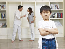 Asian boy and quarreling parents. 6-year old asian boy with quarreling parents in background Royalty Free Stock Photo