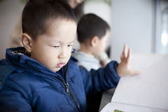 Asian boy reading book in library Stock Photos