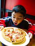 Asian Boy ready to eat a pizza. With Happy and Enjoy Royalty Free Stock Images