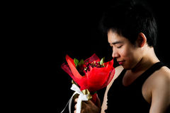 Asian boy with red bouquet in dark background Stock Images