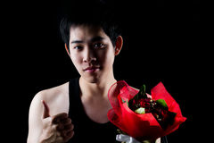 Asian boy with red bouquet in dark background Stock Photography