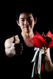 Asian boy with red bouquet in dark background Stock Photo