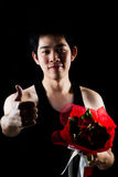 Asian boy with red bouquet in dark background Stock Photos